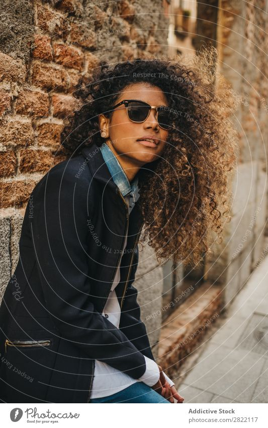 Stylish woman at brick wall Woman pretty Beautiful Ethnic Black Curly African Youth (Young adults) Stand Wall (building) Brick Street Sunglasses Brunette