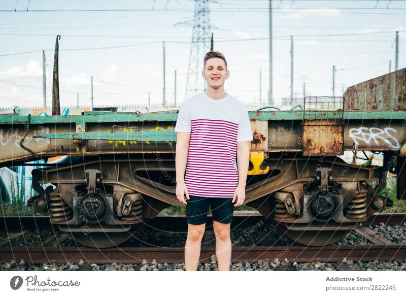 Cheerful man standing at train Man Railroad Town Stand Vacation & Travel Transport Human being Station City Youth (Young adults) Lifestyle Trip Platform Tourist