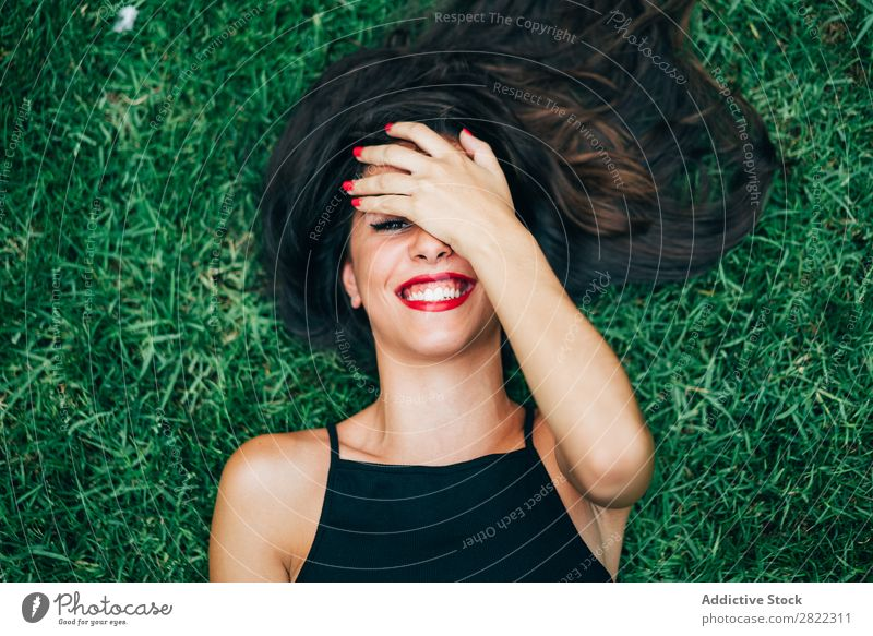 Cheerful brunette woman lying in grass Woman pretty Youth (Young adults) Beautiful Smiling Lie (Untruth) Grass Nature Looking into the camera Brunette