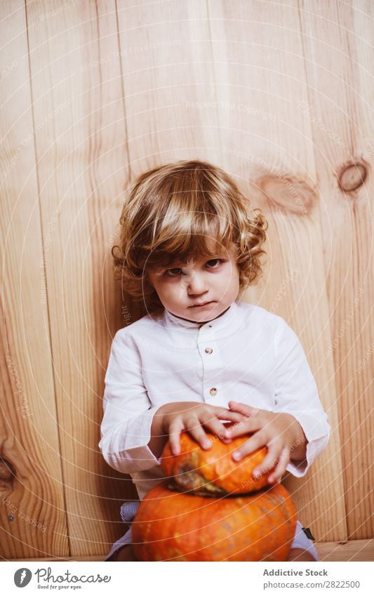 Adorable child posing with pumpkin Child Pumpkin Posture Vacation & Travel Hallowe'en Autumn human face Infancy Magic Fantasy decor Interior design Playful