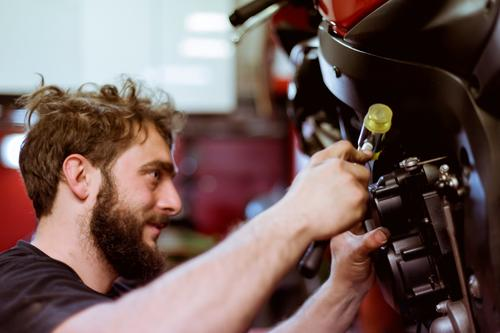 Man working on bike Maintenance Detail Part Employees & Colleagues Motorcycle Workshop Human being Engines Transport Vehicle Garage custom repair shop