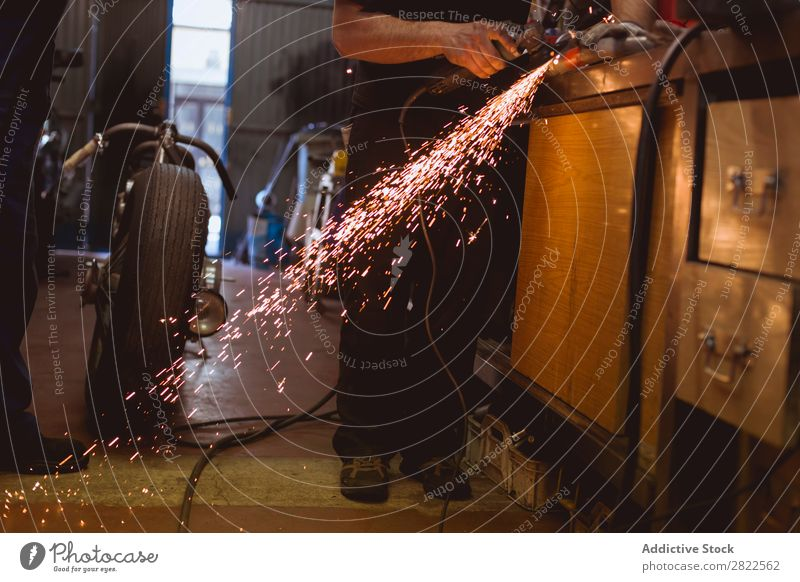 Unrecognizable worker cutting metal in garage Motorcycle Workshop Parked Engines Transport Human being Metal