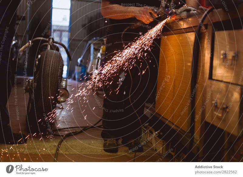 Unrecognizable worker cutting metal in garage Motorcycle Workshop Parked Engines Transport Human being Metal sparkles Vehicle Garage custom repair shop Repair