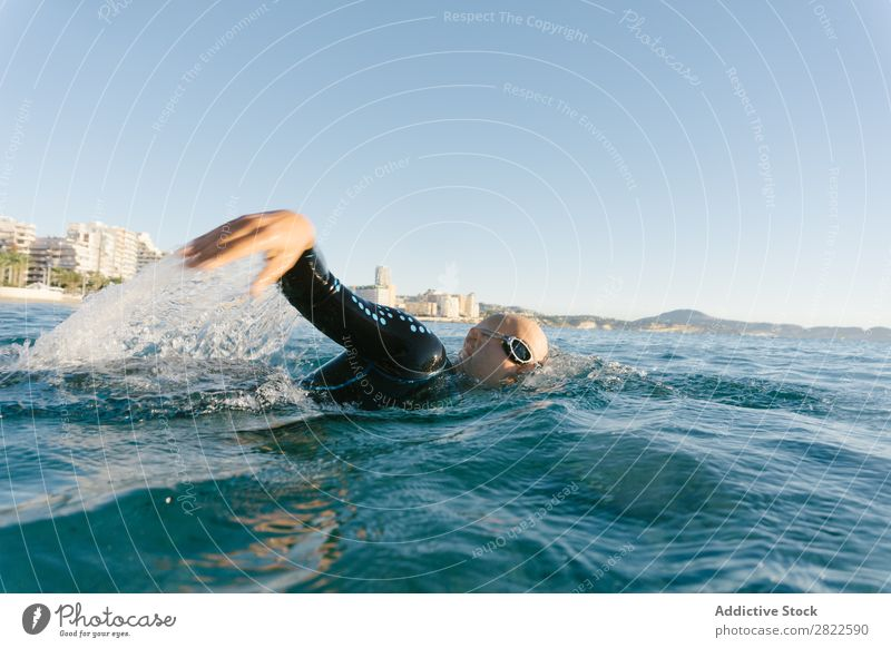 Man in wetsuit swimming in ocean Wetsuit Swimming Ocean Sports Athlete Aquatics Movement Action Water Vacation & Travel Rowing Leisure and hobbies Sunlight