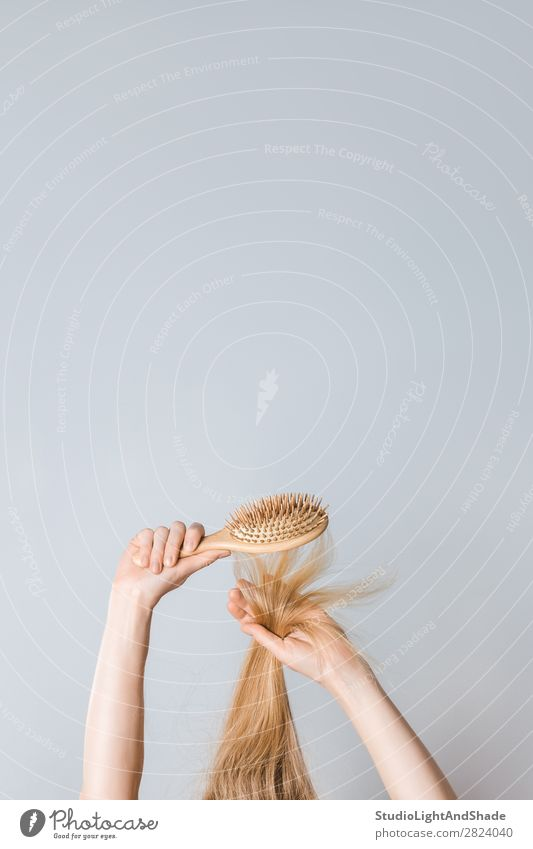 Brushing blond hair with a wooden hairbrush Lifestyle Beautiful Hair and hairstyles Health care Human being Woman Adults Arm Hand Fashion Blonde Hairbrush Wood