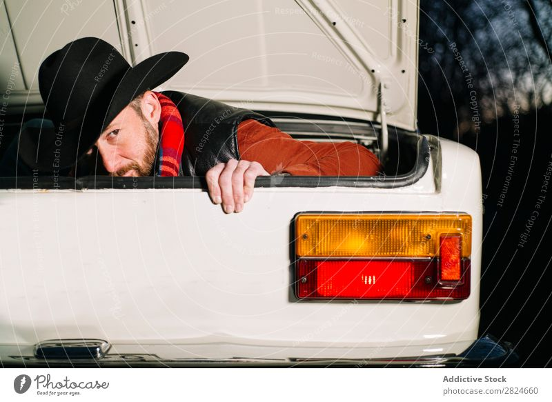 Man in trunk of vintage car Car Vintage Retro White Trunk Hat Evening