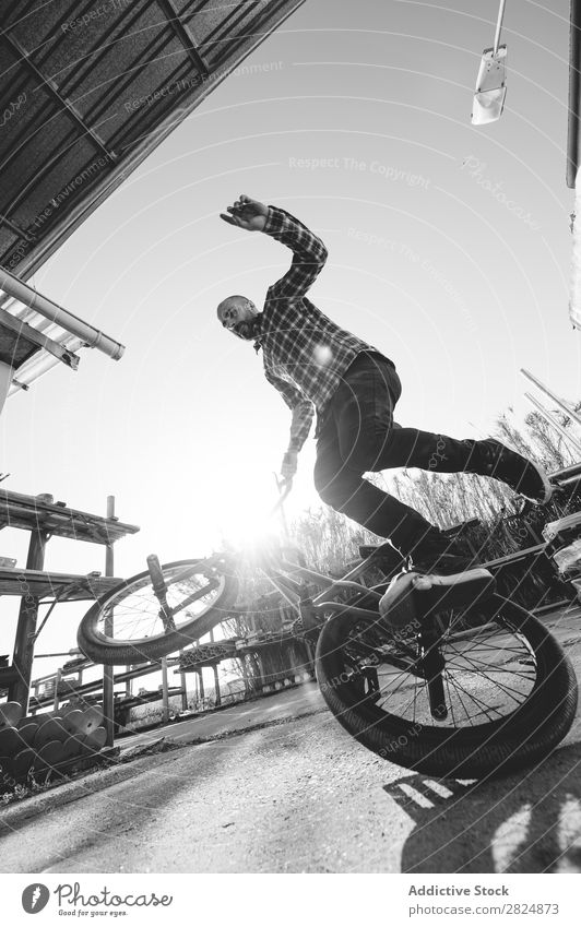 BMX rider performing tricks BMX bike Man Jump Bicycle Sports Trick Youth (Young adults) Lifestyle in motion Action Extreme Black & white photo Rider