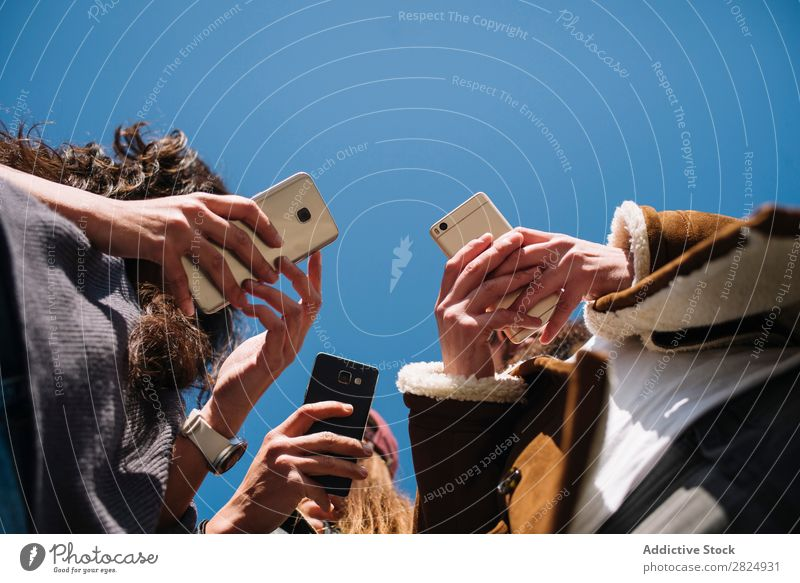 Group of friends in the street with smartphone Telephone Profile texting browsing watching video PDA Antisocial High speed Cellphone 5g wireless web page user