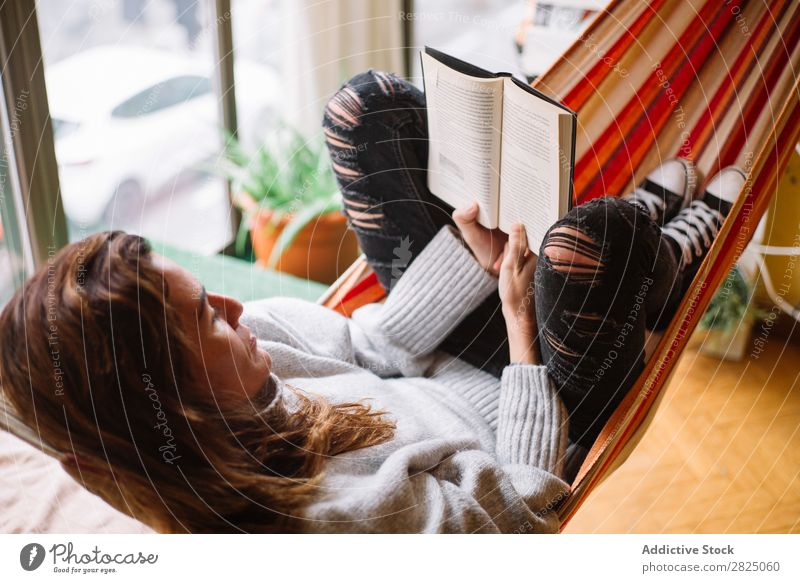 Cheerful woman lying with book Woman Home Relaxation Lie (Untruth) Hammock Reading Book Literature Lifestyle Beautiful Room Human being Easygoing Adults