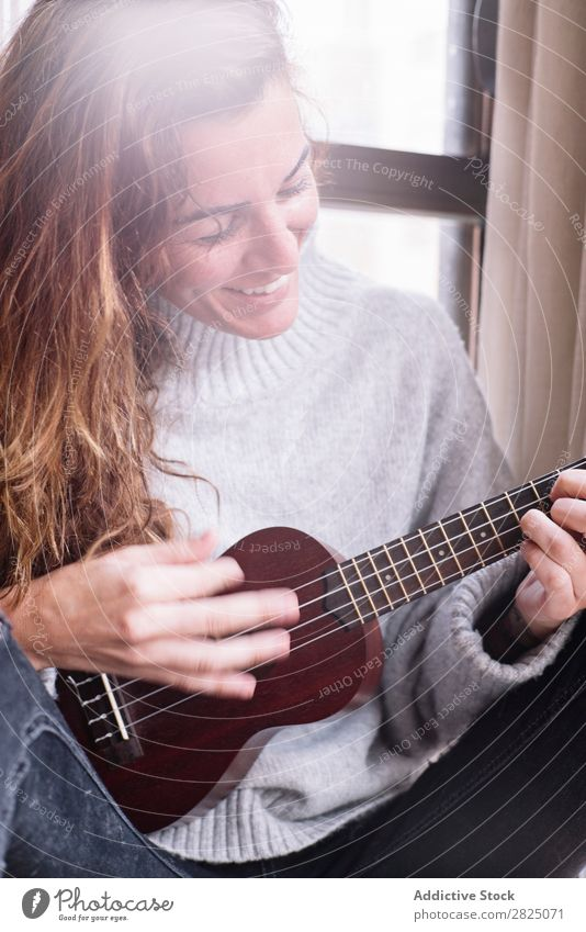 Cheerful woman playing ukulele Woman Home Relaxation Ukulele Playing Lifestyle Musician Smiling Beautiful Room Human being Easygoing Adults