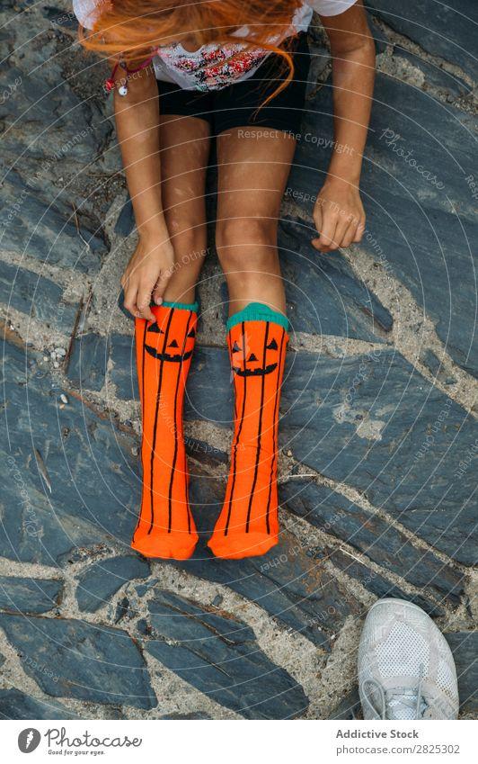 Crop girl putting on creative socks Girl Sock Wear Pumpkin Hallowe'en Autumn Child Clothing Uniqueness Vacation & Travel Fashion Multicoloured Stone Joy
