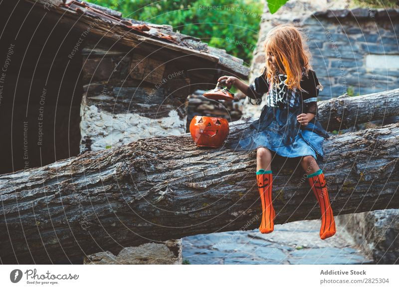 Cheerful kid in costume posing on tree Girl Costume Hallowe'en Posture Feasts & Celebrations Tradition Magic Expression