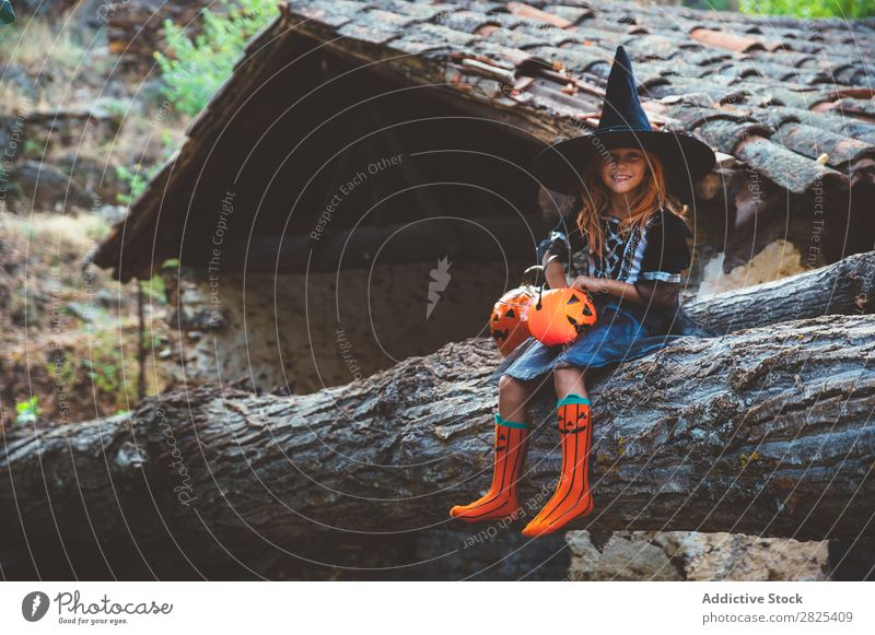 Cheerful kid in costume posing on trunk Girl Costume Hallowe'en Posture Feasts & Celebrations Tradition Magic Expression Candy Clothing Tree trunk Festival