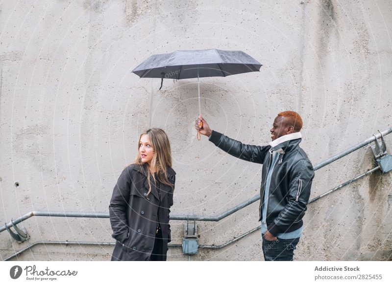 Friends who play in the street with rain. Interracial relationsh diverse Romance 20s pretty American loveliness Relationship Face Body Youth (Young adults)