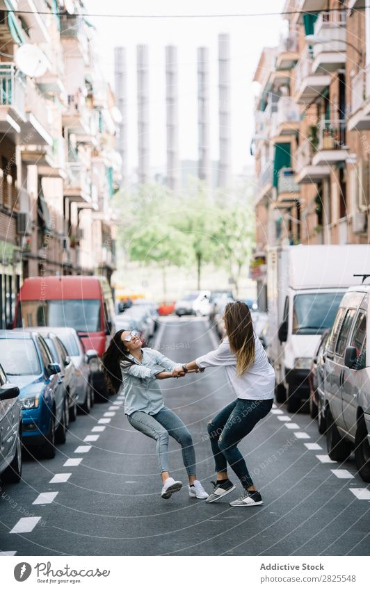 An attractive young lesbian couple on a street Woman Spinning Town having fun Hip & trendy Summer holding hands Laughter spinning round enjoyment Joy Relaxation