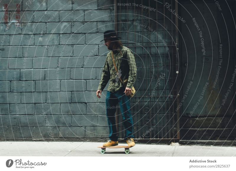 Man riding skateboard in the city Skateboard Street Stand Copy Space Cool (slang) Self-confident Hat bearded Earnest Brutal Beard Human being City Hipster