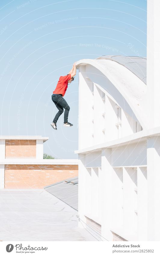 Sportive man hanging on roof sportsman Parkour Roof tracer Hanging Climbing Relaxation physical Risk rooftop motivation Action Runner Town Stunt Extreme