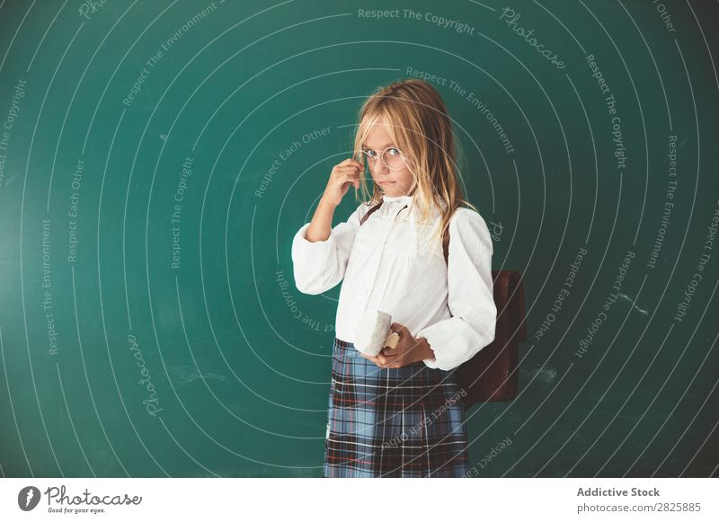 Pupil posing in classroom Girl Classroom Blackboard Stand Cheerful Book Chalk Cute Education School Grade (school level) Student Youth (Young adults) Study
