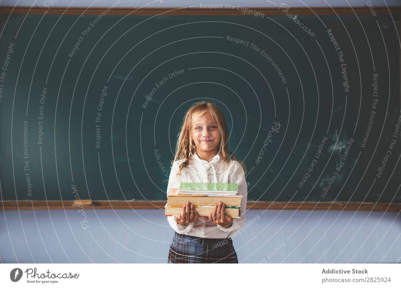Pupil at chalkboard with books in hand Girl Classroom Blackboard Stand Cheerful Happy Smiling Book Chalk Cute Education School Grade (school level) Student
