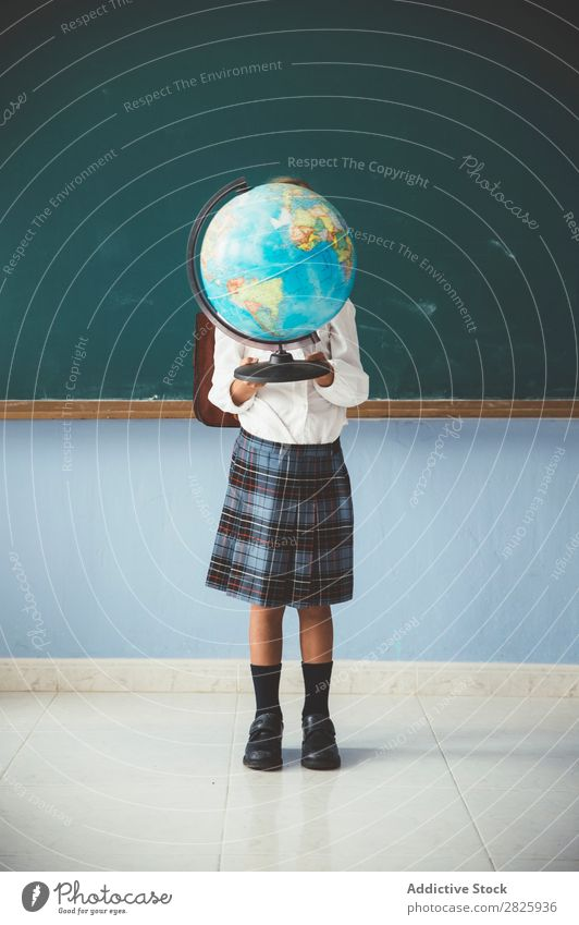 Schoolgirl covering face with globe Girl Classroom Globe Geography Cute Education Grade (school level)
