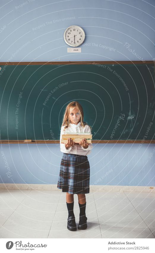 Pupil at chalkboard with books in hand Girl Classroom Blackboard Stand Cheerful Happy Book Chalk Cute Education School Grade (school level) Student