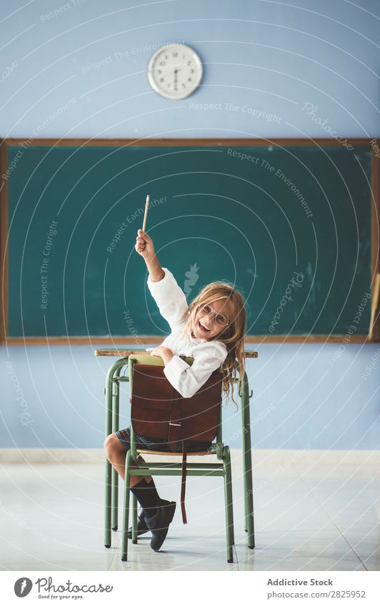 Smiling girl with pencil in class Girl Classroom Blackboard Sit Looking into the camera Pencil Happy Cheerful hand up Cute Education School Grade (school level)