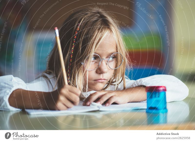 Thoughtful girl writing in class Girl Classroom Sit Desk Writing Pencil Drawing Think Considerate bored Cute Education School Grade (school level) Student