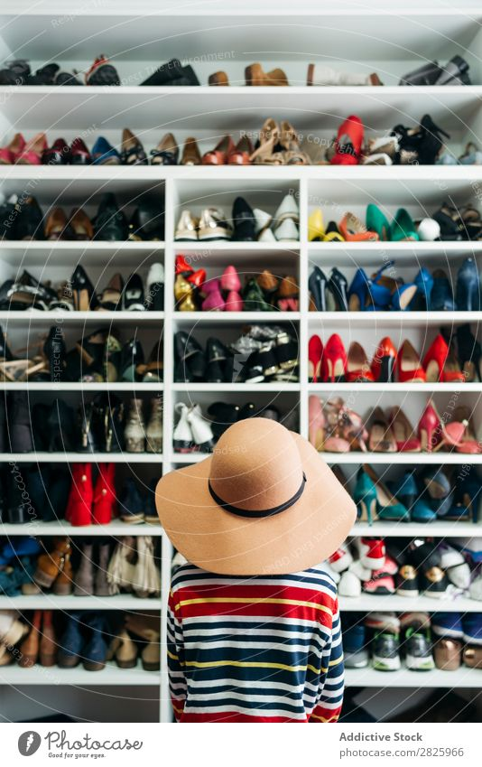Person in front of shelves with different shoes Human being Rear view Anonymous Unrecognizable Hat Rack Cupboard Footwear shelf Fashion Storage Style Closet