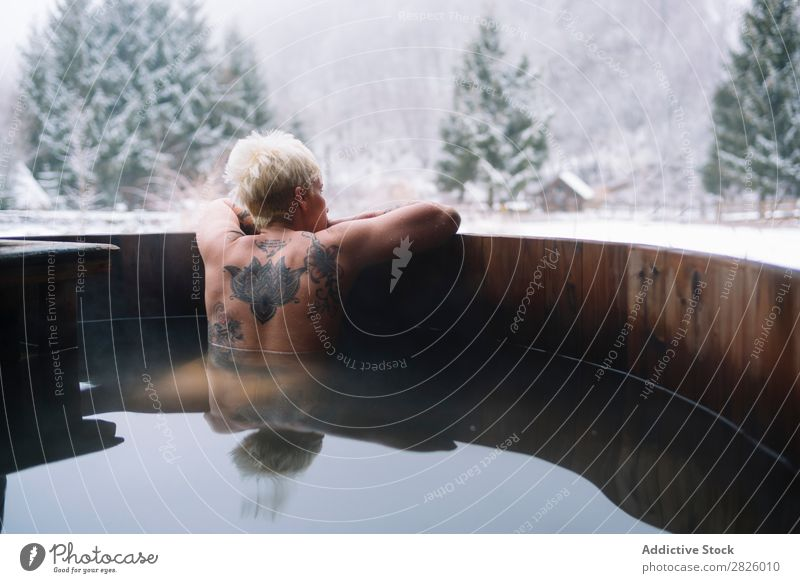 Tattooed blonde woman swimming in plunge tub Woman Swimming Nature Winter topless Water Healthy Beautiful Vacation & Travel Romania Float in the water Blonde