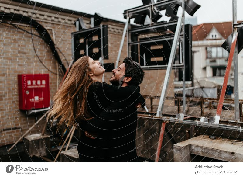 Couple hugging each other on the rooftop Embrace Cheerful City Signage Love Sit Skyline Architecture love story Town Joy Together Happy Youth (Young adults) 2