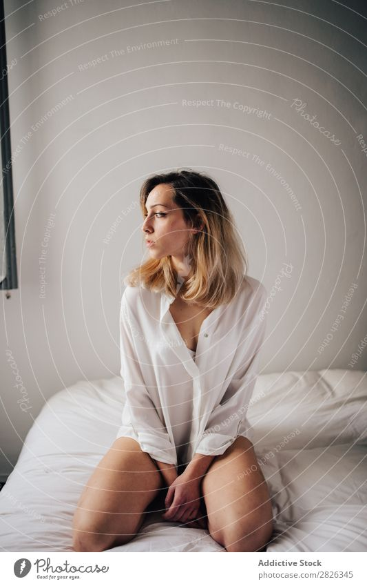 Young female sitting on a bed in white lingerie and looking away. woman morning home attractive beautiful resting lifestyle person bedroom young posing girl