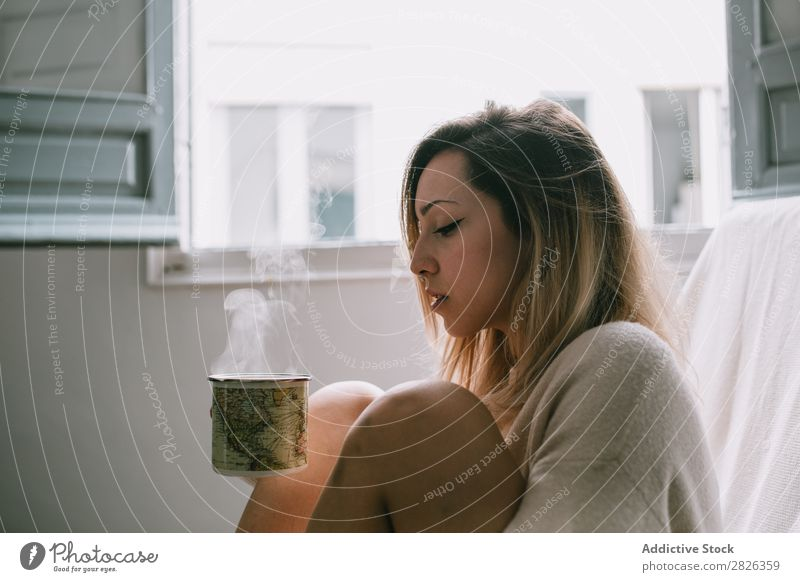 Woman having a hot drink Hot Drinking Cup Morning Beverage knees Embrace Youth (Young adults) Home Pensive Considerate Attractive Beautiful Resting Lifestyle