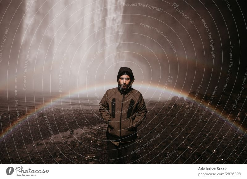 Young man in coat on waterfall Man Waterfall Rainbow Iceland Stream Fog Tourism Mountain Natural Vacation & Travel Landscape Environment Powerful Flow Energy