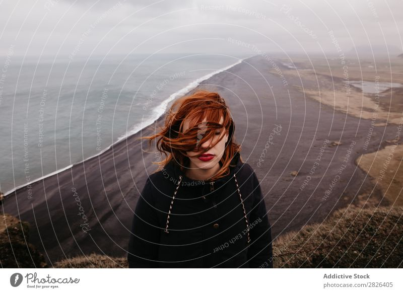 Woman with waving hair on ocean Ocean Iceland Height Landscape Vantage point Rock scenery Extreme Adventure Boundary Top Nature Stand Mountain Wilderness