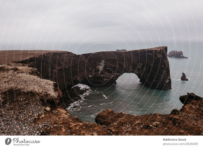 Icelandic nature wonder Man Rock Ocean Hand Height Outstretched Landscape Vantage point Coast Gloomy scenery Extreme seaside Adventure Nature Mountain