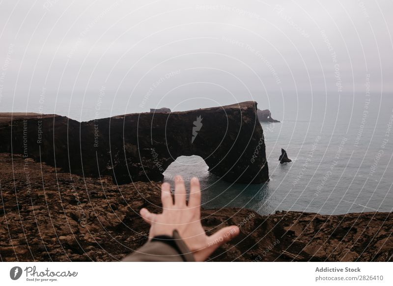 Crop hand outstretched to ocean Man Rock Ocean Iceland Hand Height Outstretched Landscape Vantage point Coast Gloomy scenery Extreme seaside Adventure Nature