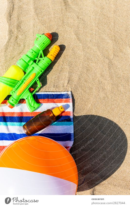 Towel, beach ball, sunscreen and water gun on the beach Child Vacation & Travel Summer Blue Green Red Sun Relaxation Joy Beach Healthy Warmth Happy Health care