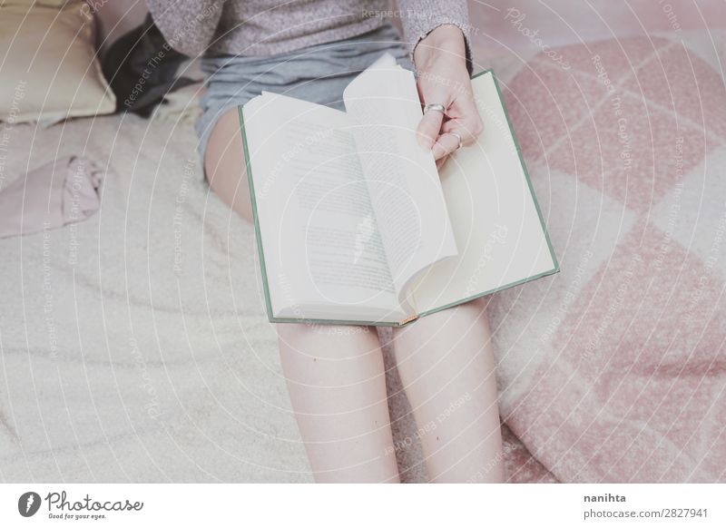 Young woman reading in her room Lifestyle Style Relaxation Calm Leisure and hobbies Reading Bedroom Education Study Student Feminine Woman Adults Legs Art
