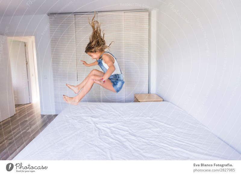 beautiful kid girl playing and jumping on bed Lifestyle Joy Happy Beautiful Leisure and hobbies Playing Reading Summer Bedroom Child Human being Feminine