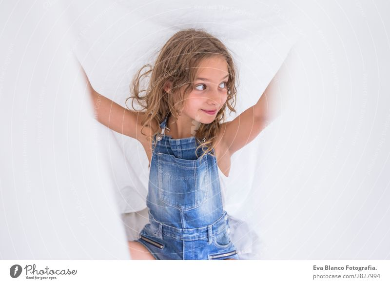 beautiful kid girl playing under white sheets on bed Lifestyle Joy Happy Beautiful Leisure and hobbies Playing Reading Summer Bedroom Child Human being Feminine