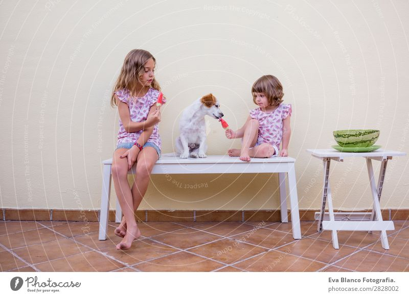 Two beautiful sister kids eating watermelon ice cream Child Human being Vacation & Travel Nature Dog Summer Green White Red House (Residential Structure) Joy
