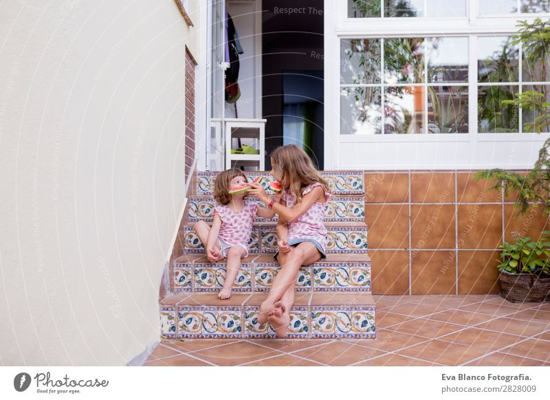 Two beautiful sister kids eating watermelon at home Child Human being Vacation & Travel Nature Summer Green White Red House (Residential Structure) Joy Girl