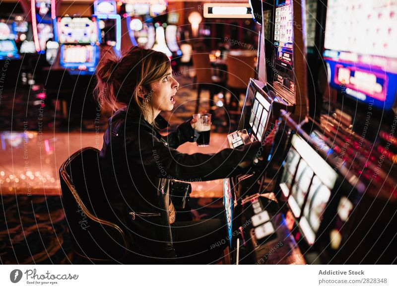 Side view of woman sitting in casino and playing slot machine. female gambling game risk luck player winner gaming gamble gambler lucky nightlife fortune