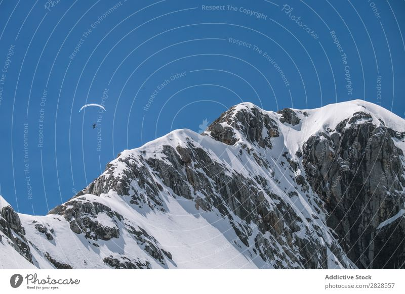 Person parachuting in mountains Parachute Mountain Snow Tourist Extreme Sports Landscape Nature Winter Human being Paragliding Gliding Action Risk Adventure