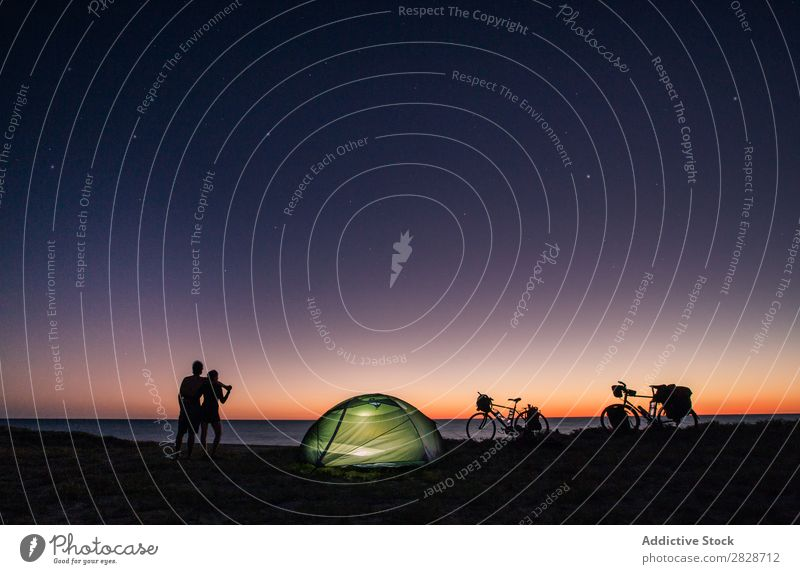 Couple with tent and bicycle on nature Coast Tourism Stars Traveling Bicycle Silhouette Cycling