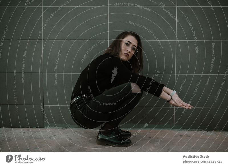 Woman sitting on hunkers pretty Youth (Young adults) Beautiful Sit Person wearing glasses Cool (slang) Looking into the camera Wall (building) Gray Brunette