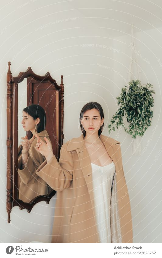 Stylish woman posing at mirror Woman pretty Youth (Young adults) Beautiful Coat Style Stand Home Flat (apartment) Mirror Reflection Posture Brunette Attractive