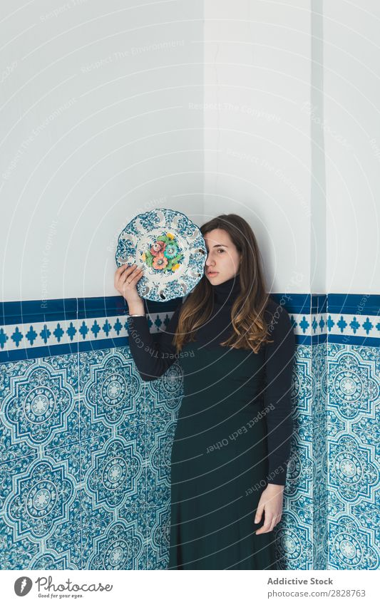 Woman standing with colorful plat pretty Youth (Young adults) Beautiful Stand Wall (building) Tile Plate Blue Dish Posture Foyer Brunette Attractive Human being