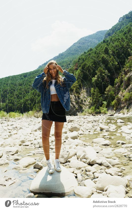 Happy girl posing on the stones of a river Woman Posture traveler trekking Tropical Mountain Rock Paradise Hiking enjoyment Tourism River Summer pose
