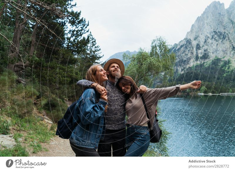 Happy friends in mountains Woman Man Mountain Joy Posture Together Smiling Hiking Lake Water embracing Cheerful Vacation & Travel Adventure Tourist